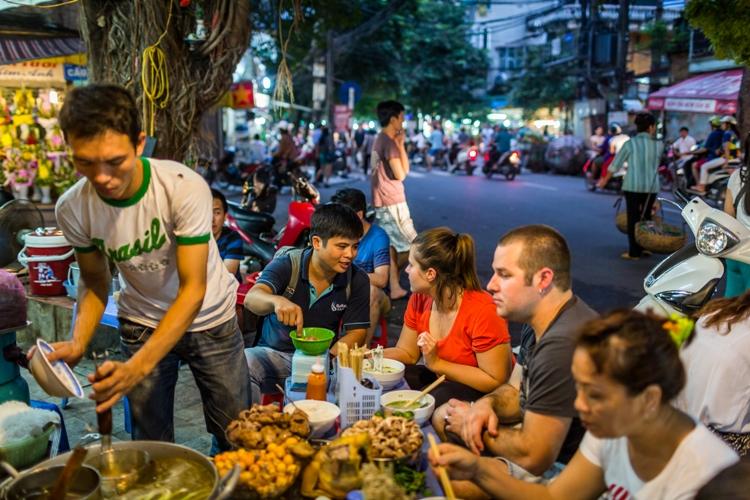 Food tourists enjoying local street food in Hanoi